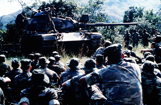 Marine Corps infantrymen of Company B, 1ST Battalion, 3rd Marines, 3rd Marine Division, Fleet Marine Force, are given classes on the M60A1 tank. The crewmen of the tank, from the 1ST Marine Division, are giving the classes
