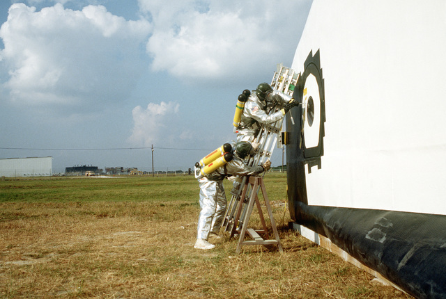 Two pararescuemen from the 38th Aerospace Rescue and Recovery Squadron wear fire-protection gear as they try to enter the mockup Columbia during an off-runway mishap exercise. The exercise is one of several planned to optimize rescue and recovery operations for the space shuttle Columbia