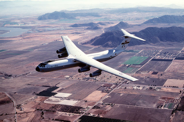 AN air-to-air left front view of a C-141B Starlifter aircraft over Norton Air Force Base