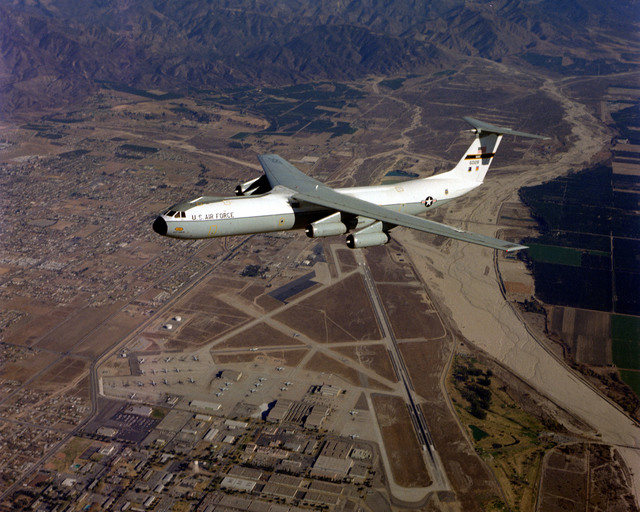 An air-to-air left side view of a C-141 Starlifter aircraft over Norton Air Force Base