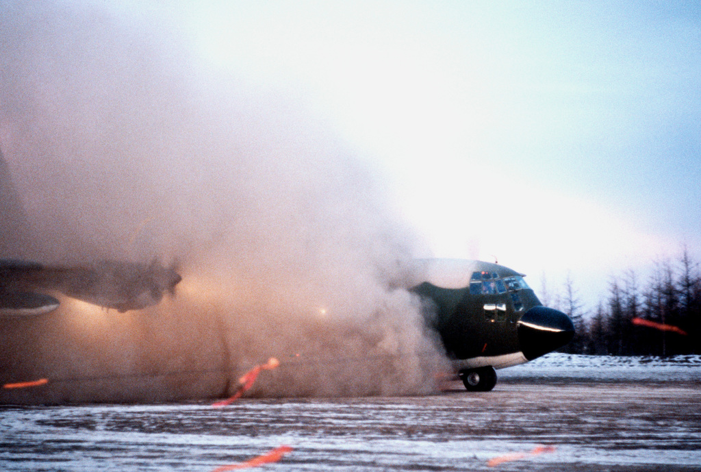 A C-130 Hercules aircraft lands on an unpaved runway at the camp base during Exercise Brim Frost '81
