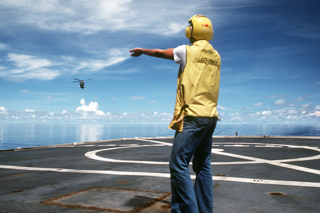 A crewman from Helicopter Light Antisubmarine Squadon 31 (HSL-31) signals to the pilot of an HH-2D Seasprite helicopter approaching the deck of the surveying ship USNS CHAUVENET (T-AGS 29)