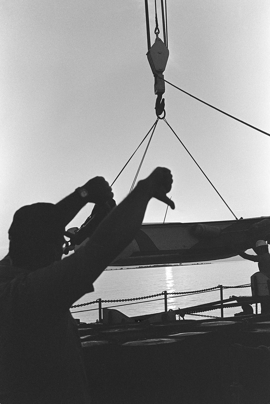 A crewman signals for a boat to be lowered from the surveying ship USNS CHAUVENET (T-AGS 29)