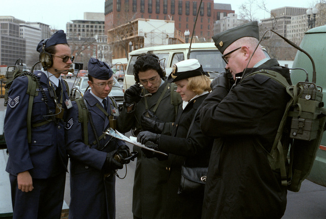 A female Navy officer coordinates the radio communications of two Air Force staff sergeants and an Army specialist during rehearsal for Inauguration Day. Also standing with the group is an Army sergeant major who is talking on the portable radio that he is carrying on his back