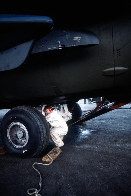 A ground crew chief inspects the landing gear of an F-111A aircraft. The 366th Tactical Fighter Wing airman is participating in Exercise Brim Frost '81