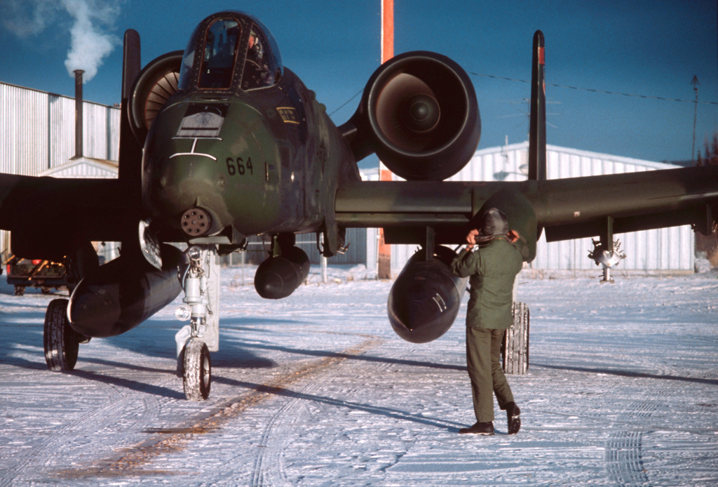A ground crew chief marshals an A-10 Thunderbolt II aircraft into a parking position during Exercise Brim Frost '81