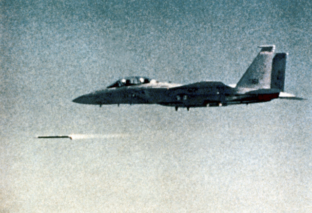 A left rear view of an F-15 Eagle aircraft firing an advanced medium range air-to-air missile