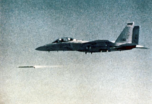 A left rear view of an F-15 Eagle aircraft firing an advanced medium range air-to-air missile
