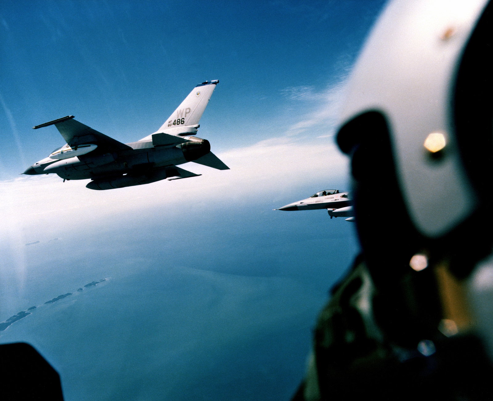 A left side view of two F-16A Fighting Falcon aircraft, seen from inside another Falcon's canopy, in flight. The aircraft are from the 35th Tactical Fighter Squadron, 8th Tactical Fighter Wing, being deployed to Kunsan Air Base, Korea. The leading aircraft is shown equipped with a luggage pod on the left wing and auxiliary fuel tanks