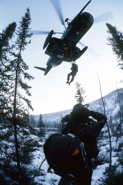 "A rescueman on a jungle penetrator is lowered from a hovering CH-3 Jolly Green Giant helicopter to pick up a ""downed"" pilot during survival training. The 71st Aerospace Rescue and Recovery Squadron helicopter is participating in exercise Brim Frost '81"