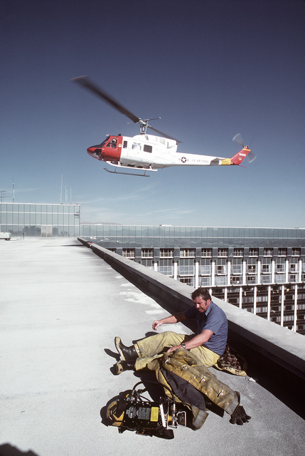 A UH-1N Iroquois helicopter descends to the top of the MGM Grand Hotel as an exhausted fire fighter rests. The helicopter, 56th Fighter Weapons Wing, is involved in a mission to rescue guests from the burning hotel