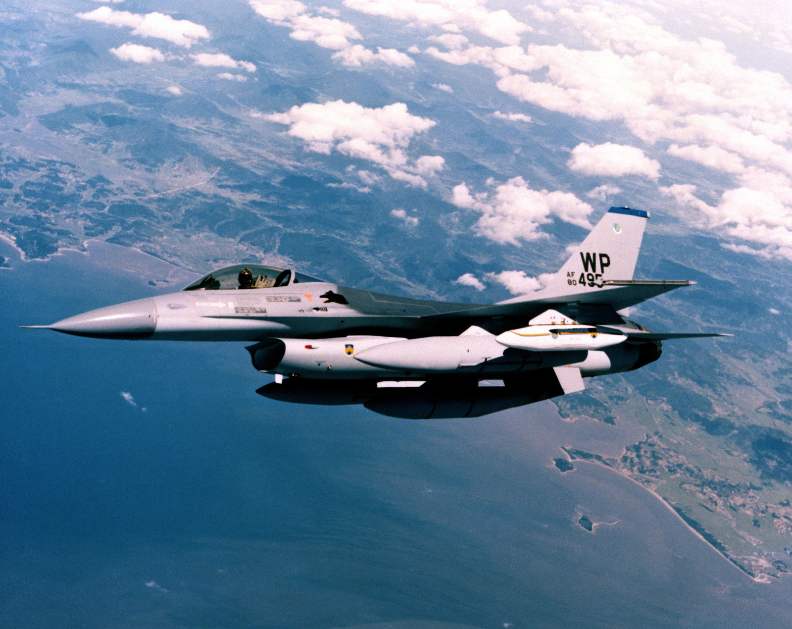 A view of an F-16A Fighting Falcon aircraft banking to the right during deployment to Kunsan Air Base, Korea. The aircraft is from the 35th Tactical Fighter Squadron, 8th Tactical Fighter Wing. The aircraft is equipped with a luggage pod on the left wing and auxiliary fuel tanks