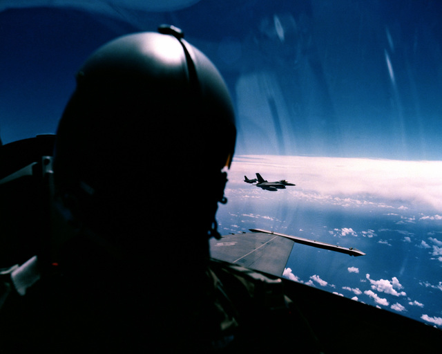 A view of an in-flight F-16A Fighting Falcon aircraft pilot, with other Falcons shown in the background. The aircraft are from the 35th Tactical Fighter Squadron, 9th Tactical Fighter Wing, being deployed to Kunsan Air Base, Korea