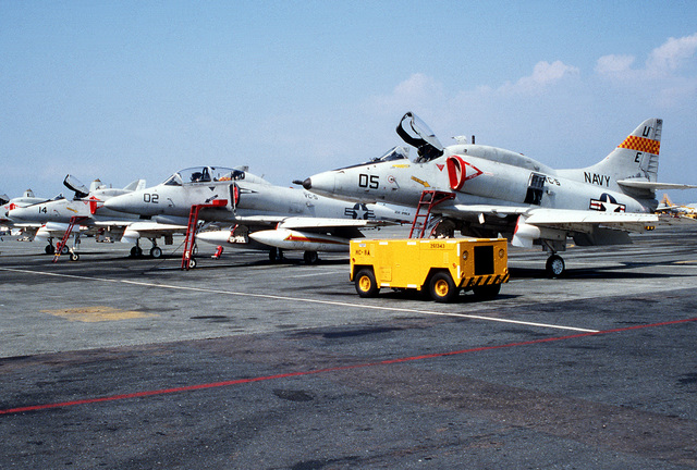 A view of Fleet Composite Squadron 5 (VC-5) A-4 Skyhawk aircraft parked on the flight line. A TA-4J is second from the right, the other three are A-4Es. An NC-8A Mobile Electric Power Plant (MEPP) is in the foreground
