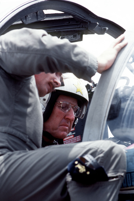 ADM Thomas B. Hayward, CHIEF of Naval Operations, sits in the cockpit of an A-6E Intruder aircraft. He is briefed prior to flight by a pilot from Medium Attack Squadron 115 (VA-115) off the aircraft carrier USS MIDWAY (CV-41)