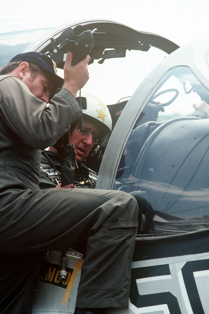 Admiral Thomas B. Hayward, CHIEF of Naval Operations, sits in the cockpit of an A-6E Intruder aircraft. He is being briefed by a pilot from Medium Attack Squadron 115 (VA-115) assigned to the aircraft carrier USS MIDWAY (CV 41), prior to flight