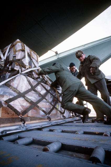 """Airmen load a pallet of cargo aboard a C-141 Starlifter aircraft during Exercise Brim Frost """"81"""