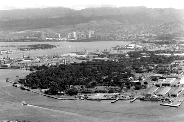 An aerial view of the naval shipyard in the foreground. Aiea in the background and the USS ARIZONA Memorial in between, near Ford Island