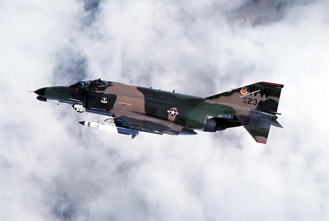 AN air-to-air left side view of an F-45G Phantom II aircraft carrying an AGM-78 Standard Arm missile on its right wing and an ALQ-119 electronic countermeasures pod on its left wing