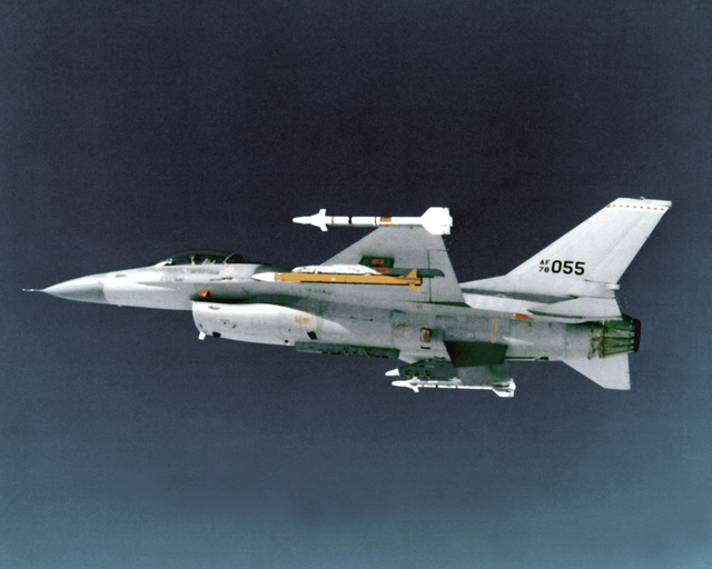 AN air-to-air left underside view of an F-16 Fighting Falcon aircraft carrying a yellow advanced medium-range air-to-air missile and AIM-9J Sidewinder missiles on the wing tips