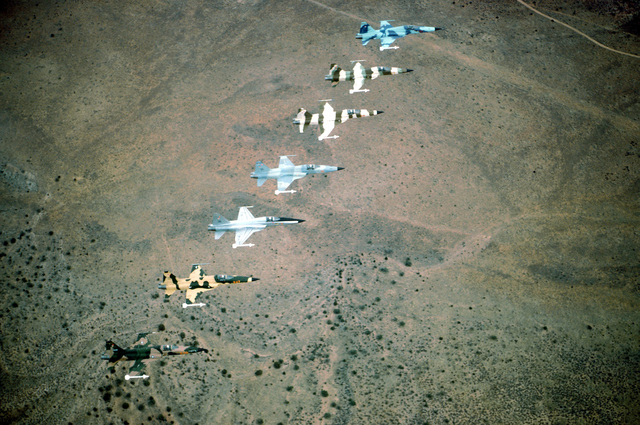 AN air-to-air overhead view of a seven-ship echelon formation of F-5E Tiger II aircraft from the 57th Fighter Weapons Wing over a desert. Each aircraft is painted in a different camouflage scheme and is carrying one AIM-9 Sidewinder missile