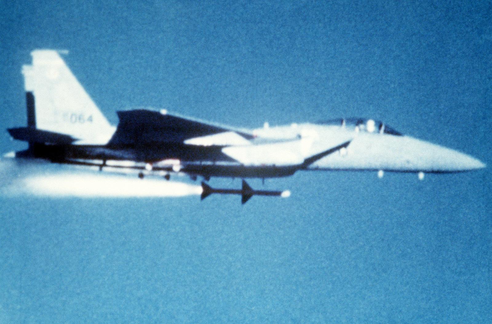 AN air-to-air right side view of an F-15 Eagle aircraft firing an AIM-7 Sparrow missile