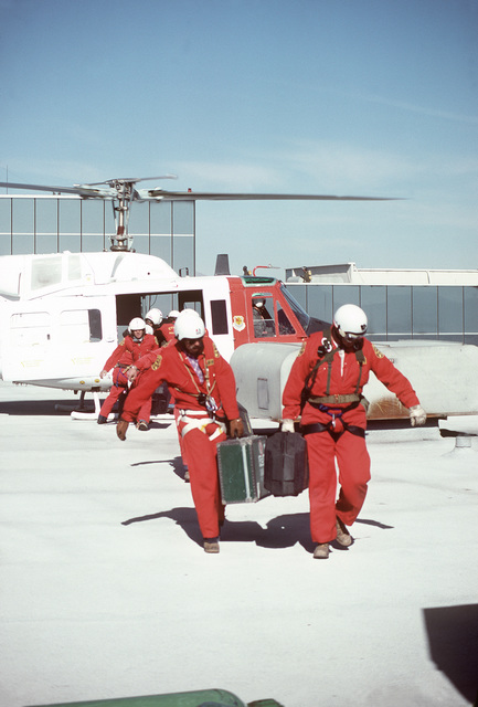 Crewmen unload emergency medical equipment from a UH-1N Iroquois helicopter upon arrival on the top of the MGM Grand Hotel. The crew, 57th Fighter Weapons Wing, is involved in a mission to rescue guests from the burning hotel