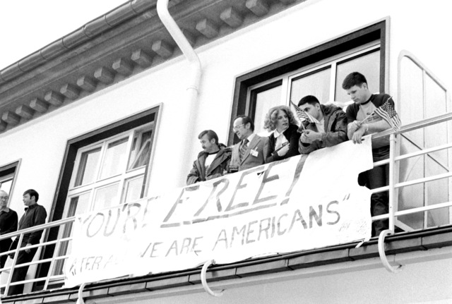 Former hostages Army MSGT Regis Ragan, Richard Morefield, Marine SGT William Gallegos and Marine SGT Paul Lewis, left to right, watch the German Children's Chorus street concert honoring the hostages from a hospital balcony. The 52 hostages are spending a few days in the hospital after their release from Iran prior to their departure for the United States