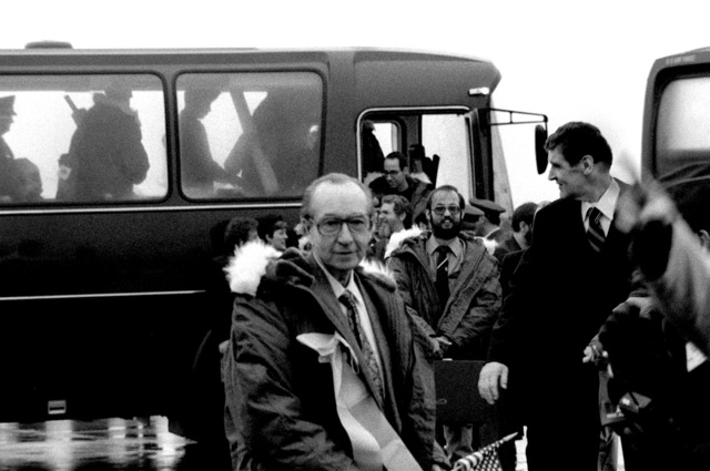 Former hostages Robert C. Ode and Donald Cooke, left to right, wearing winter coats, arrive at the base for their departure to the United States. The 52 hostages were hospitalized for a few days after their release from Iran