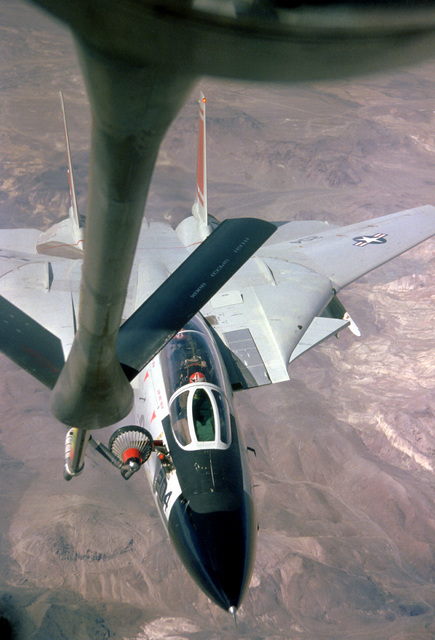 Front view of an F-14 Tomcat aircraft being refueled by a tanker aircraft in flight, as seen from the boom operator's section