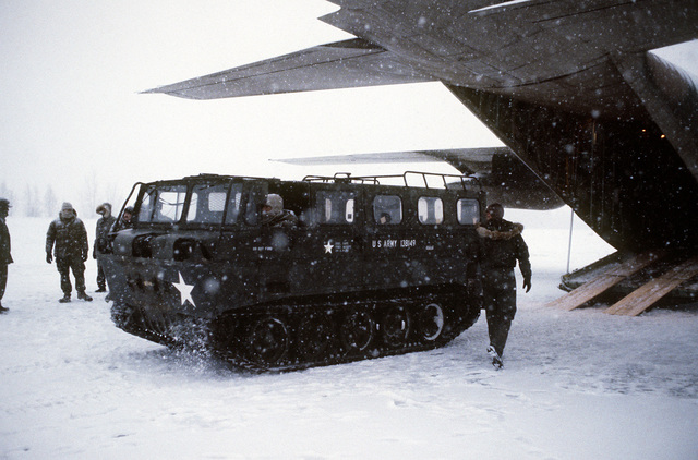 Green Beret troops move a tracked personnel carrier, called a Snow Cat, from a C-130 Hercules aircraft, in a runway assault practice during a snowstorm. The practice session is part of exercise Brim Frost '81. The Green Beret troops are assigned to Co. C, 2nd Bn., 7th Special Forces