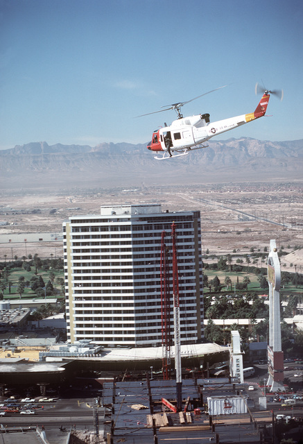 Left rear view of a UH-1N Iroquois helicopter, in flight, circling down into the city. The aircraft, 57th Fighter Weapons Wing, is involved in a mission to rescue guests from the MGM Grand Hotel (not in photo), on fire