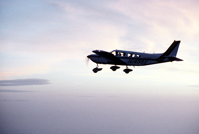 Left side view of a Piper Arrow aircraft, silhouetted against the sunset, in flight. The aircraft belongs to the base's Aero Club