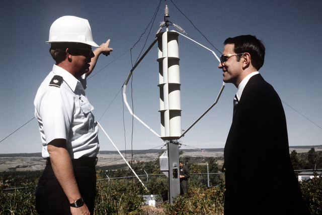 LTC E. Kullgren explains an energy collecting vertical wind turbine, being constructed, to CPT William A. Tolbert