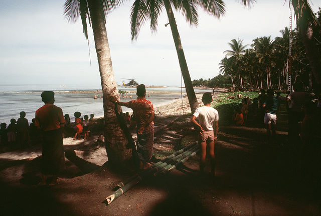 Natives watch as an HH-2D Seasprite helicopter from Helicopter Light Antisubmarine Squadon 31 (HSL-31) nears the shore