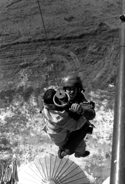 Pararescueman A1C Lawrence Davis, on a jungle penetrator holding an injured man, is being hoisted up from atop a grain elevator into a hovering helicopter. Davis is from the 40th Aerospace Rescue and Recovery Service, Air Force Rescue Coordination Center