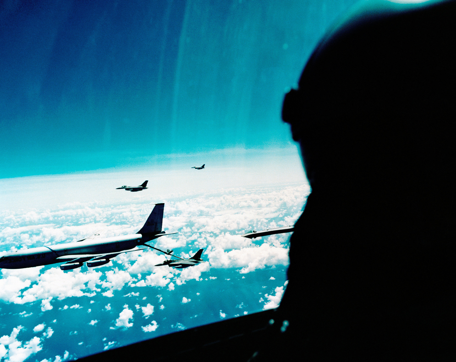 Right side view of a KC-135 Stratotanker aircraft and F-16A Fighting Falcon aircraft, seen from inside another Falcon's canopy, in flight. The KC-135 is refueling one of the aircraft during deployment to Kunsan Air Base, Korea. The Falcons are from the 35th Tactical Fighter Squadron, 8th Tactical Fighter Wing