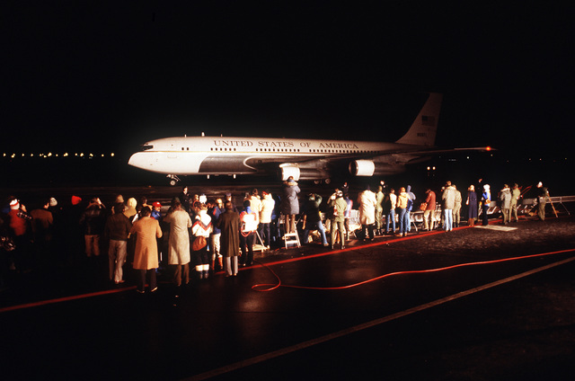 Spectators watch one of two C-137B Stratoliner aircraft that are bringing in the 52 freed hostages after their release from Iran