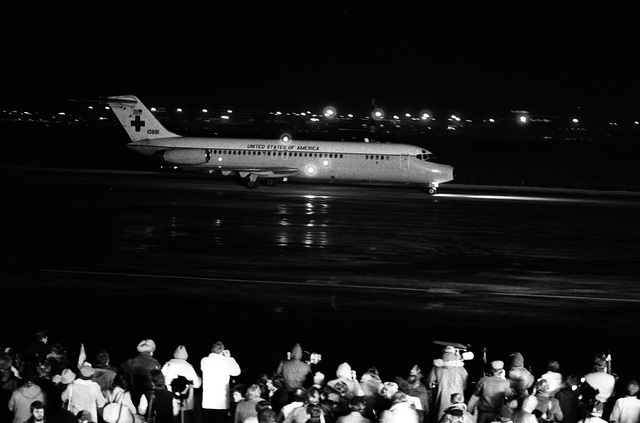 Spectators watch one of two C-9 Nightingale aircraft bringing in the 52 freed hostages after their release from Iran