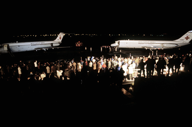 Spectators watch two C-9 Nightingale aircraft bringing in the 52 freed hostages after their release from Iran