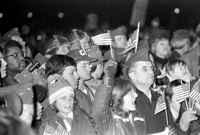 Spectators wave and cheer as two C-9 Nightingale aircraft bring in the 52 freed hostages after their release from Iran