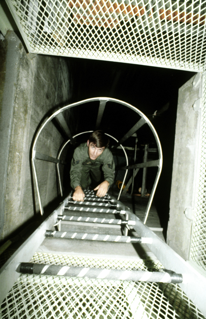 SSGT David Pierce crawls down the ladder to the combat crew capsule. Pierce is a manager of a missile launch control facility, 91st Strategic Missile Wing, Strategic Air Command