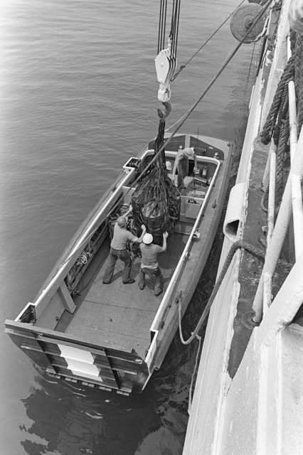 Supplies are loaded aboard a Navy landing craft, vehicle and personnel (LCVP) from the surveying ship USNS CHAUVENET (T-AGS 29). The LCVP is being used to transport supplies to navigational aid sites