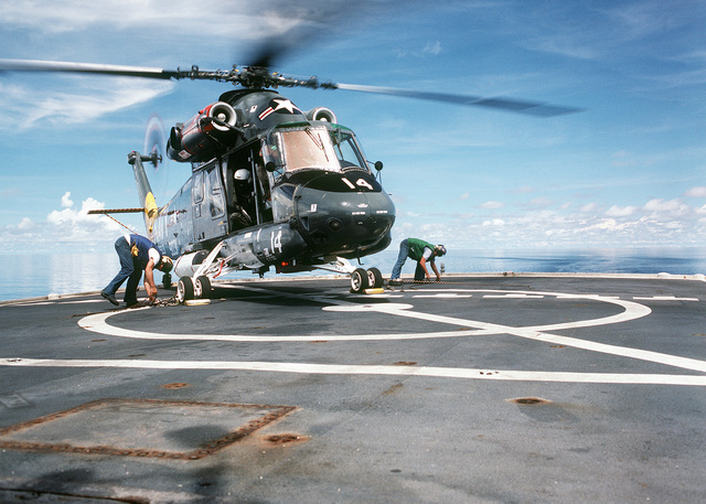 Tie down chains are removed as an HH-2D Seasprite helicopter from Helicopter Light Antisumarine Squadon 31 (HSL-31) prepares to take off the surveying ship USNS CHAUVENET (T-AGS 29)