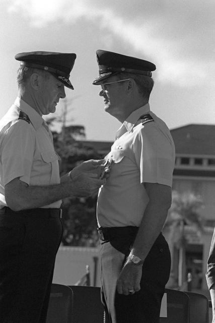 US Air Force (USAF) Lieutenant General (LGEN) James D. Hughes, Commander in CHIEF (CINC), Pacific Air Forces (PACAF), awards a medal to USAF Major General (MGEN) Hoyt S. Vandenberg, Jr., Vice CINC, PACAF, during MGEN Vandenberg's retirement ceremony