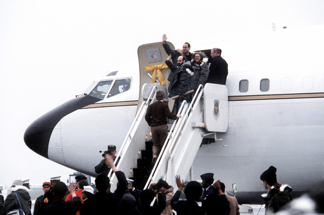 Victor Tomseth, Barry Rosen and Ann Swift, left to right, on the steps to the VC-137 Freedom One aircraft wave at the crowd before boarding. These are three of the 52 former hostages departing for the United States after their release from Iran
