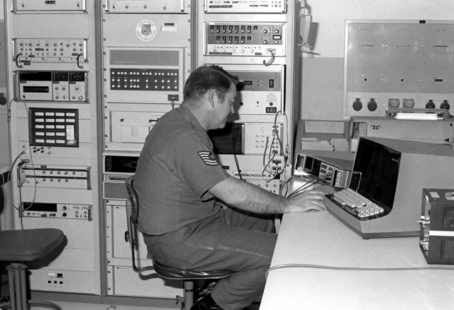 A technical sergeant uses a computer to calibrate a voltmeter
