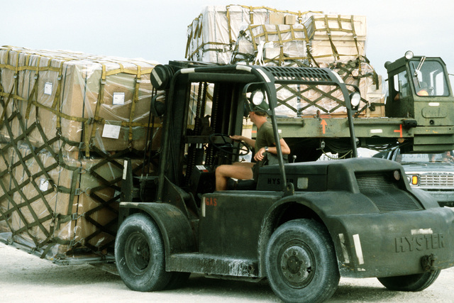 A side view of a forklift carrying cargo pallets during Airlift Operations Project '81. The activities are being held by the Military Airlift Command