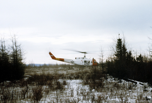 A right side view of an Army UH-1 Iroquois helicopter being used to shuttle Army personnel and supplies during exercise Brim Frost