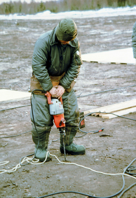 SSGT George Schaffer uses an electric drill to make holes in the frozen ground for tent stakes during exercise Brim Frost